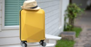 Yellow Rolling Luggage with a straw hat on top in front of a white home.